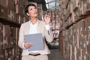 Warehouse manager checking her inventory in a large warehouse